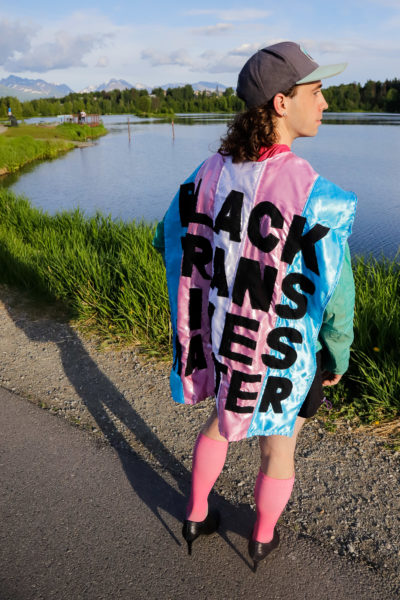 """a person wearing sports clothes, high heels and a cape that indicates """"BLACK TRANS LIVES COUNTING"""" pose in front of a body of water"""