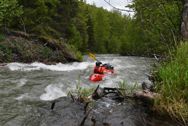 A red packraft in a creek