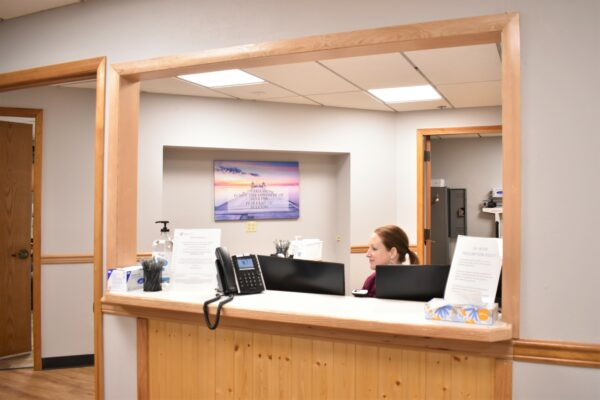 a woman sits at a desk behind a reception counter