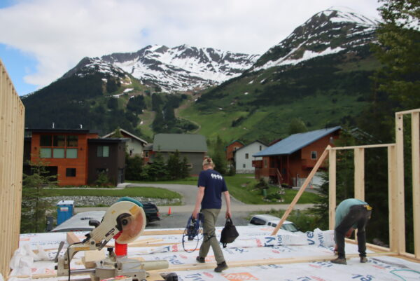 People walk on a construction area in fornt of some suburban houses and a snow covered mountain.