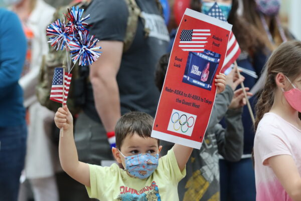 A young boy holds an american flag and a poster