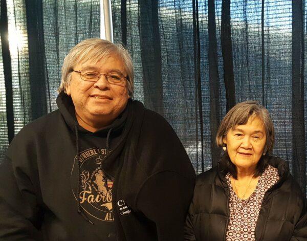 An Alaska Native man in a black sweathshirt next to a woman in a black coat