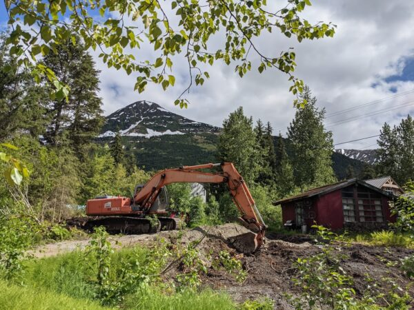 A backhoe digs a hole next to a red little house in front of a mountain