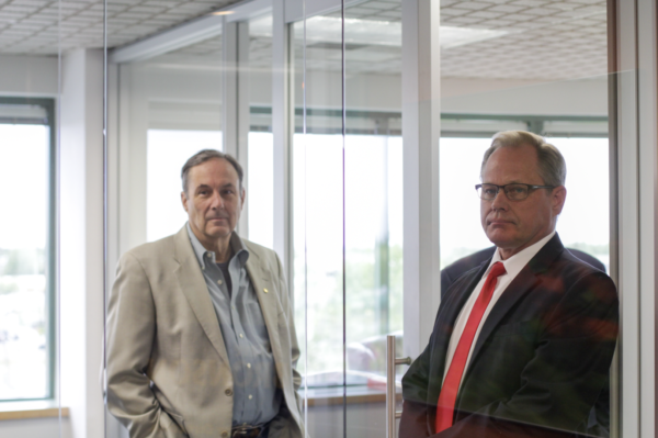 Two men stand looking at the camera behind a glass door