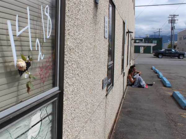 A broken window on the side of a tan building with two people sitting on the street corner nearby