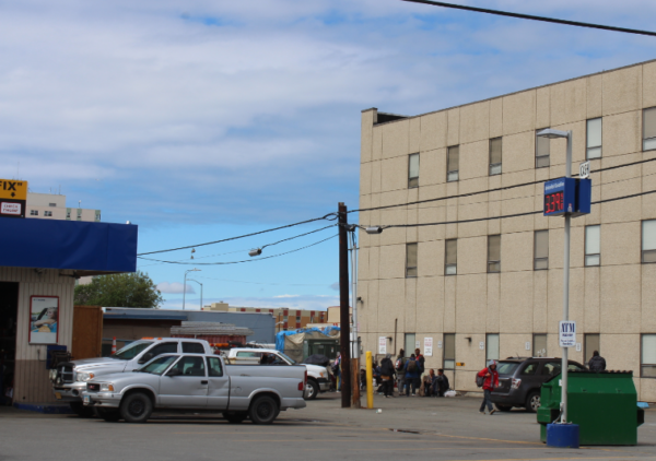 A gas station garage next to a parking lot in front of a tan building where people are gathered