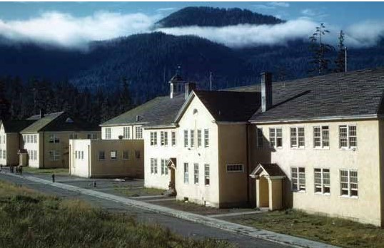 A white building with a black roof in front of some steamy mountains