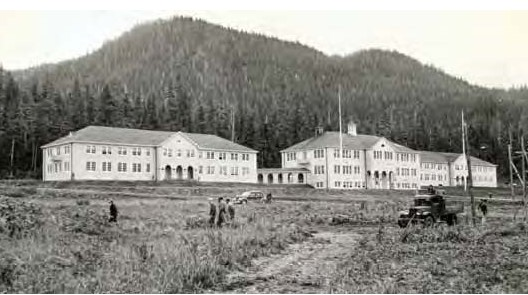 A black and white photo of a large white building in front of some mountains