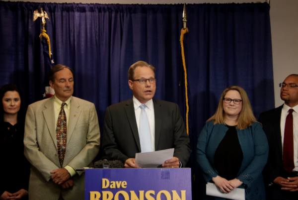 """A white man speaks at a podium in front of a blue """"Dave Bronson sign"""" On his left is a white man with a tan suit, on his right is a white woman with a blue jacket and blond hair"""