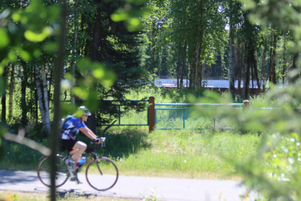 A biker on a paved path by some woods