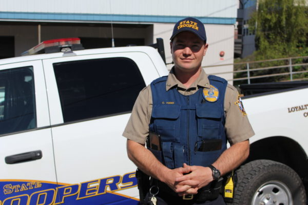 A white man wearing a state trooper uniform stands in front of a white truck with his hands clasped in front of him.