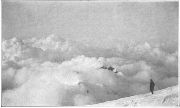 A person on a mountain above some clouds in a black and white photo