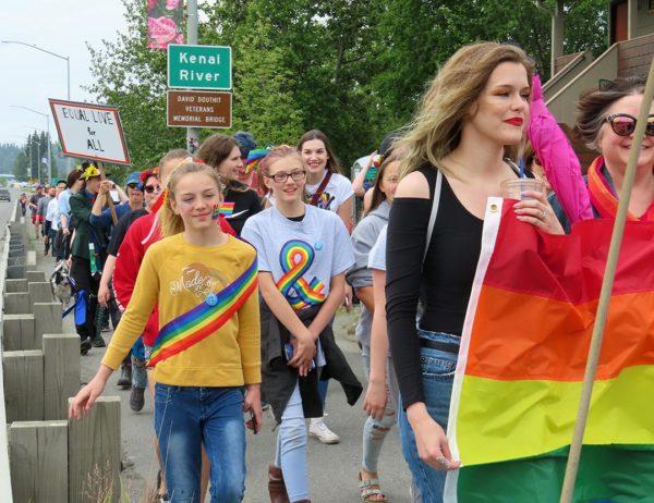 People wearing rainbow clothes walks down a sidewalk