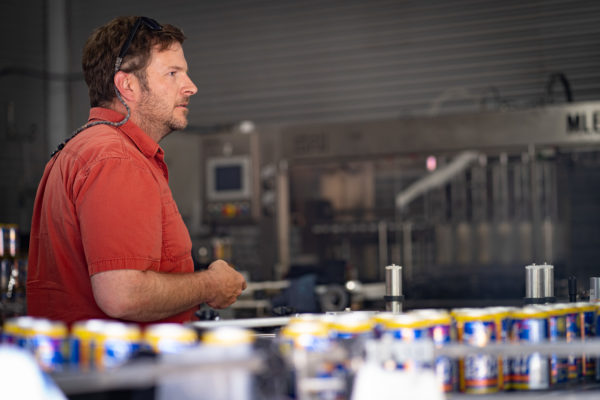 A man stands behind a line of beer cans moving down a conveyer belt.