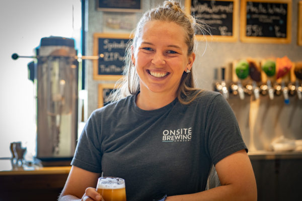 A woman stands in front of beer taps, holding a glass of beer in her hand.