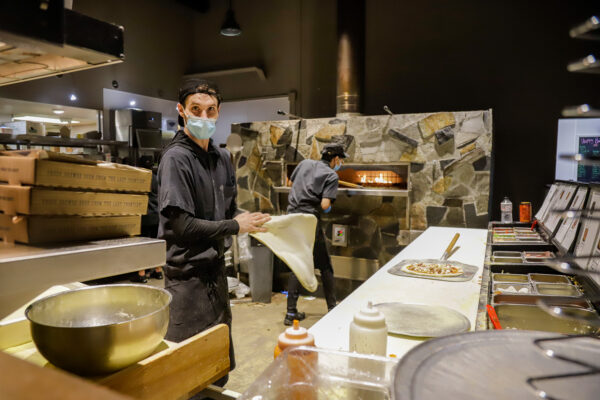 two people preparing pizzas in front of a pizza oven in a restaurant