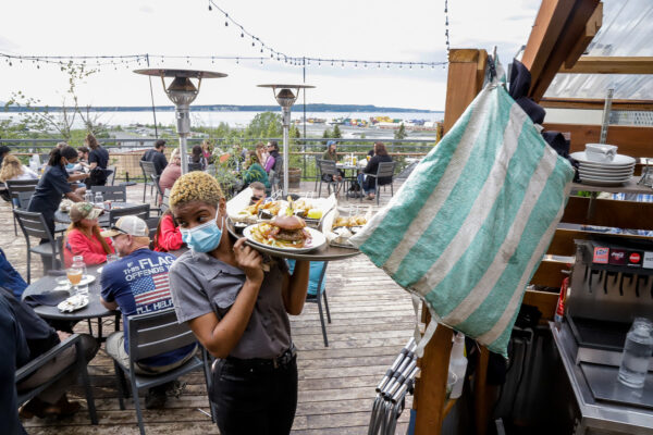 a person holds a tray of food on a restaurant deck