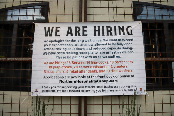 """a sign posted outside a restaurant reads """"we are hiring"""""""