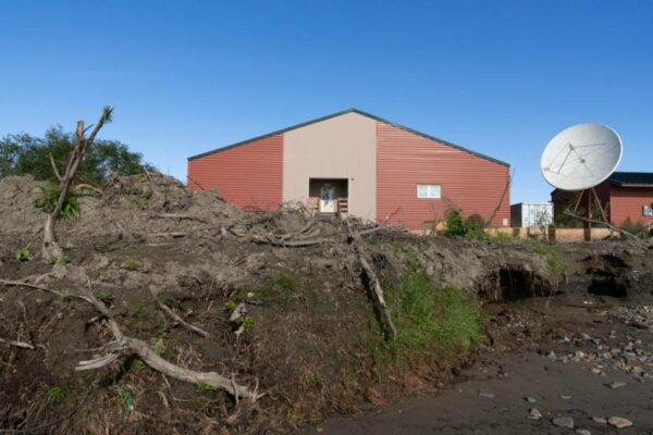 A red building on top of an eroding river bank