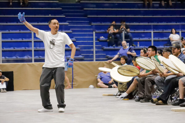 a person dances while others drum on an arena floor