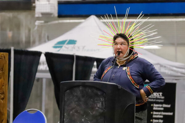a person on stage performs while wearing a headdress made of neon zip ties