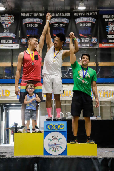 three people stand on a competition podium
