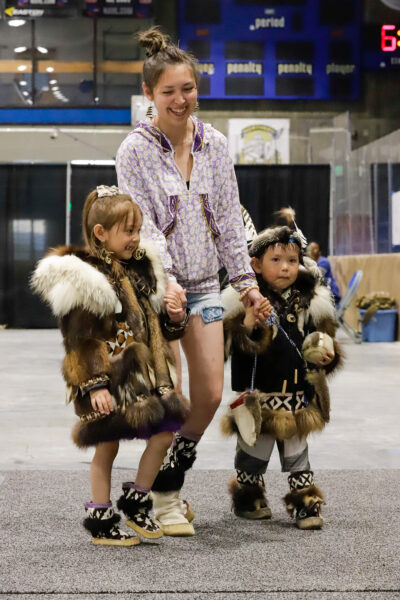 two kids, accompanied by an adult, model their regalia