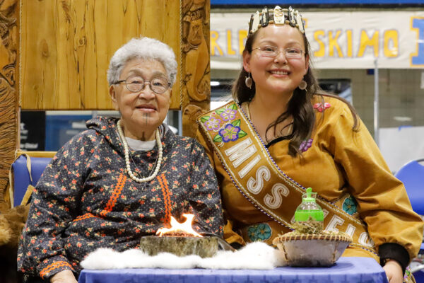 an elder and a pageant winner pose for a photo behind a seal oil lamp