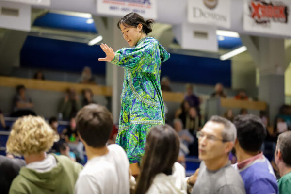 a person prepares to ascend while others pull during a blanket toss demonstration