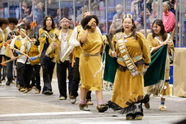 people in regalia drum and dance on an arena floor