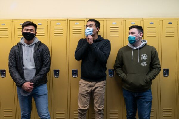 Three students in front of yellow lockers