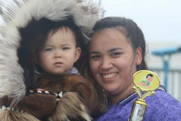 A woman in a kuspuk with a baby in a fur ruffed parka