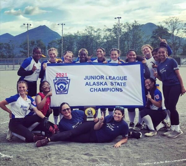 A group of girls and women stand around a sign that says Junior League Alaska State Champions.