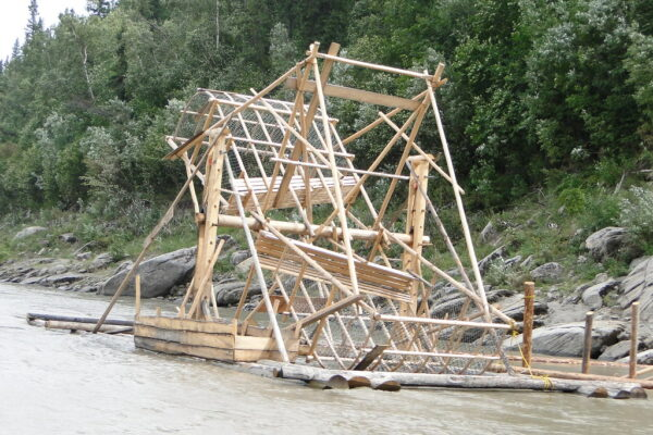A wooden fish wheel on a large river