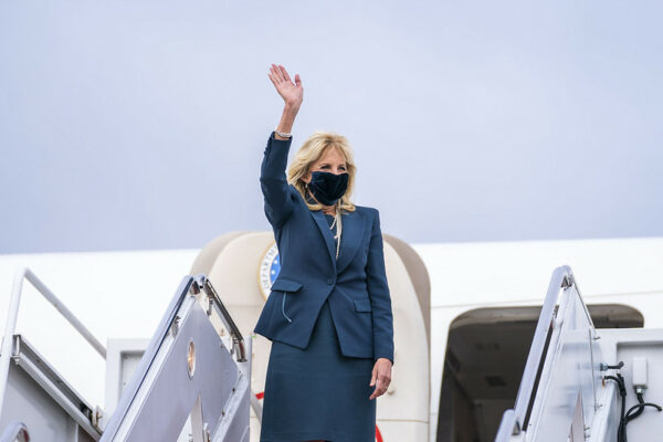 A blond woman waves while getting off a plane