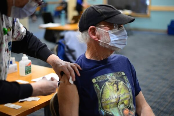A man with a white beard gets a shot in the shoulder