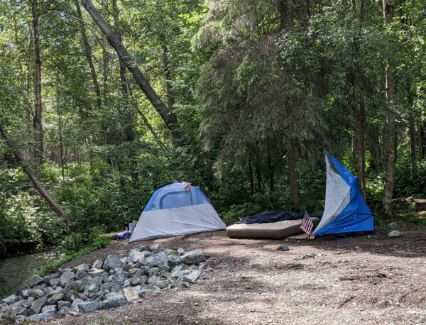 A tent on a dirt trail next to a creek