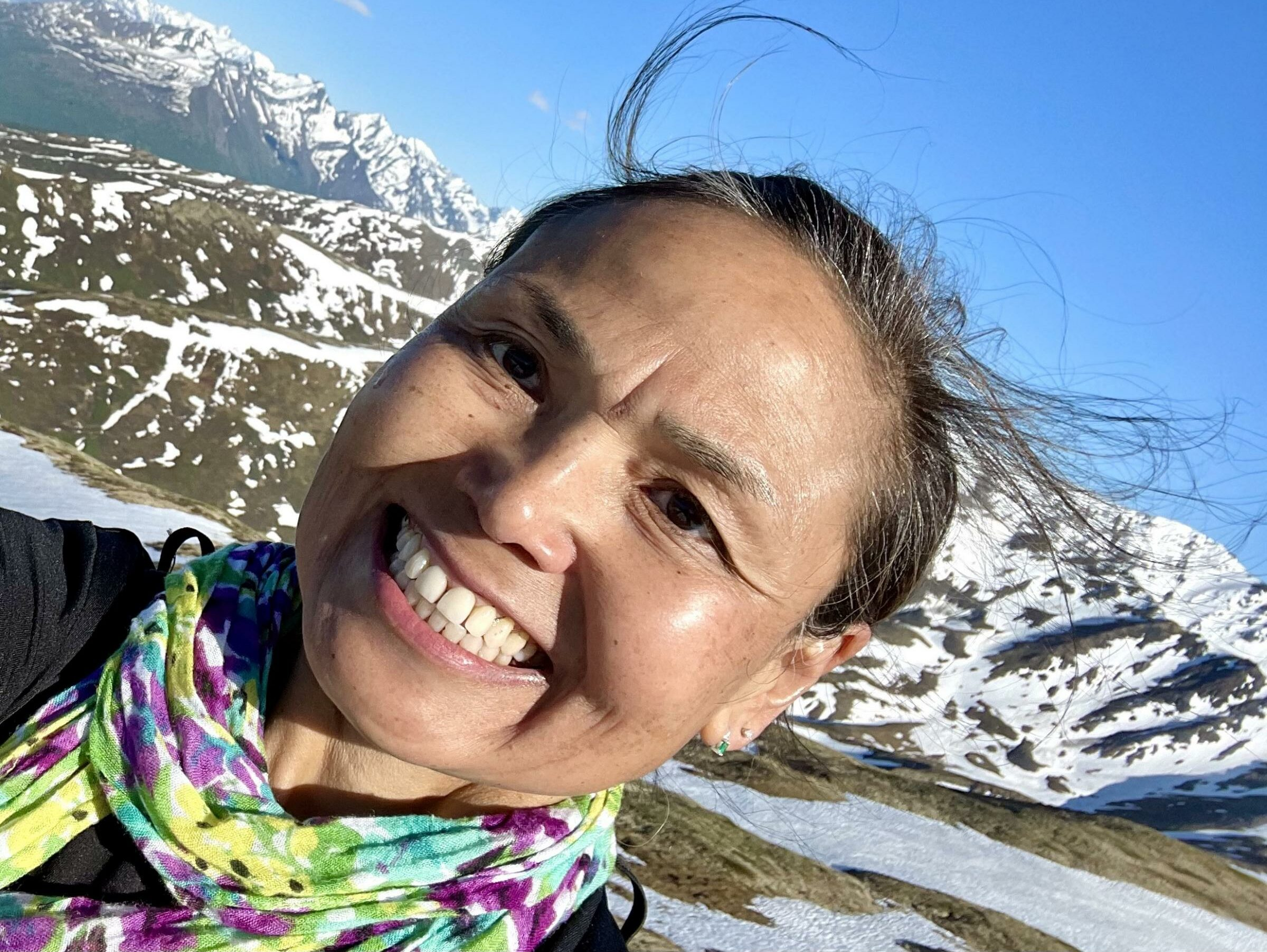 A woman smiles into a camera for a selfie in front of some snowy mountains