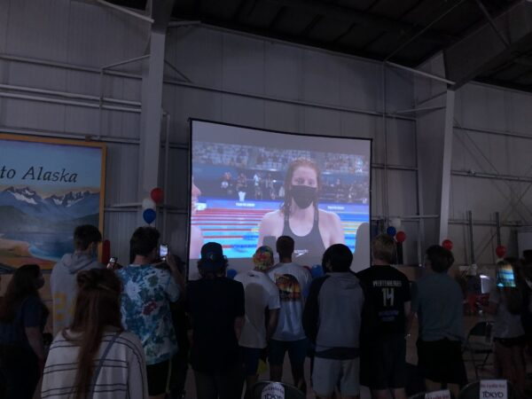 A group of people stand in a big room watching a screen with a swimmer's image projected on it.