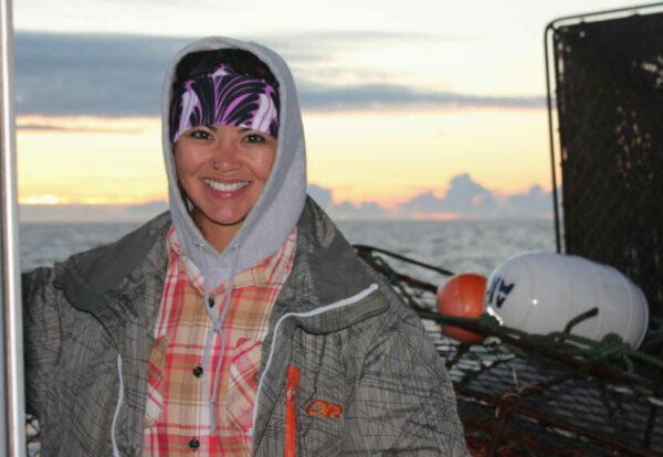 A woman ina gray sweatshirt on a boat
