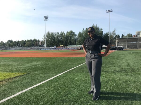 A woman in a baseball umpire's uniform stands with her hands on her hips on the third baseline of a baseball diamond.