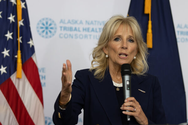 A woman in a blue blazer holds a microphone and talks in front of a U.S. and Alaska flag.