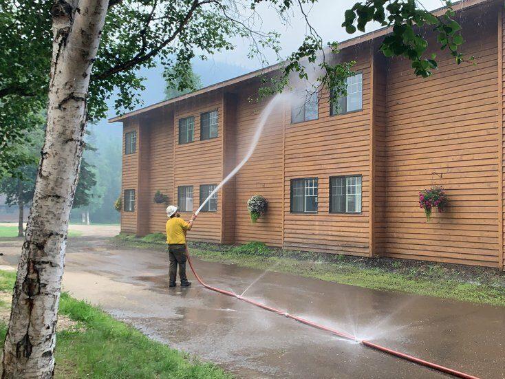 A firefighter sprays a tan buildings with a hose