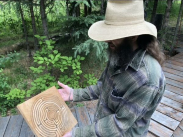 A man in a flannel shirt, a white straw hat holds a board of wood with a circular labyrinth design with some forest in the background