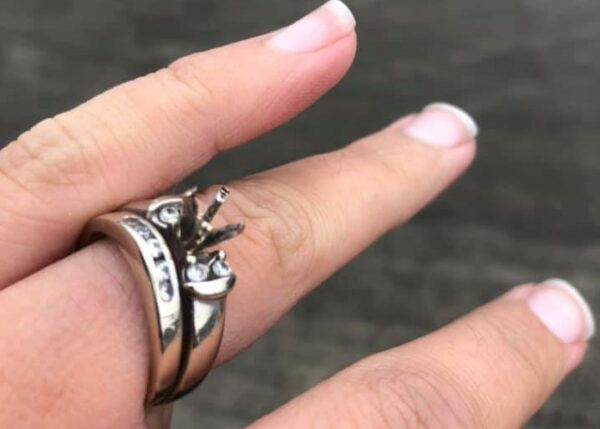 An engagement ring on a finger is missing the diamond.