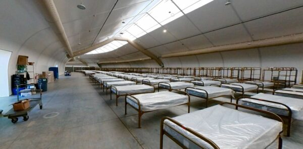 Dozens of cots in three rows span from the foreground into the distance.