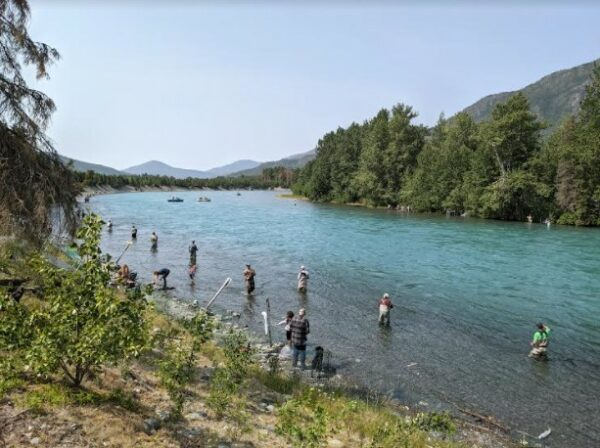 People in aders in a large river fishing with poles