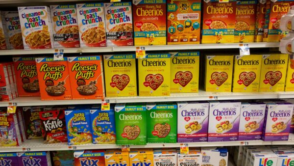 Grocery store shelves filled with boxes of a variety of cereal brands.
