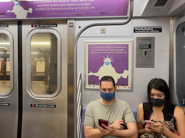 Two people on a subway looking at their cell phones wearing masks