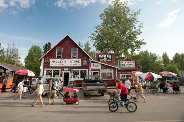 A street view of people walking and biking in front of a red general store.